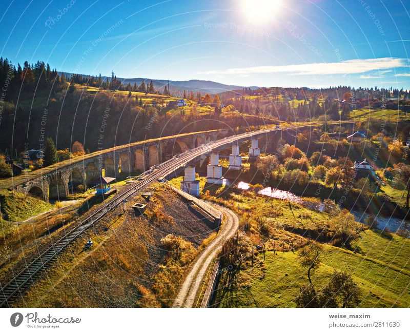 Old railway viaduct in mountains. Autumn Rural Landscape Sky Vacation & Travel Nature Blue Green Red Sun Tree House (Residential Structure) Clouds Leaf Forest