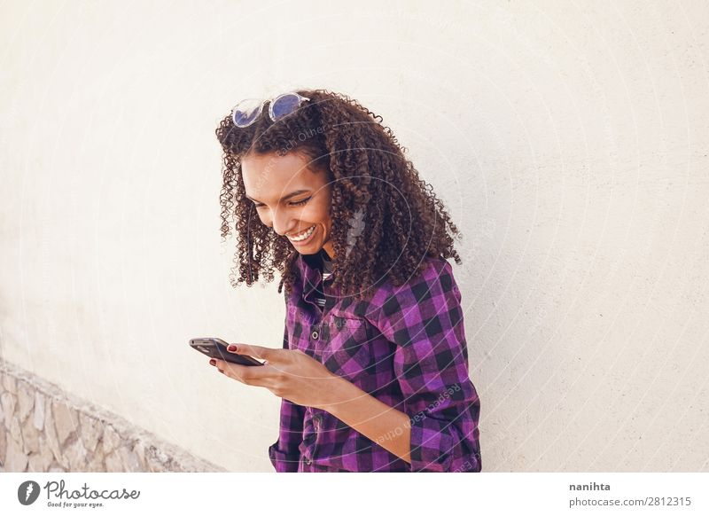 Young casual woman using her smartphone Woman Human being Youth (Young adults) Young woman Joy Black 18 - 30 years Adults Natural Feminine Emotions
