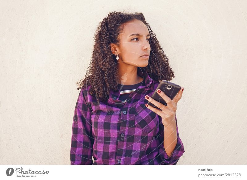 Young casual woman using her smartphone youth cool wifi internet technology call message communication young teen black african afro american diversity