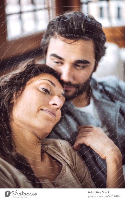 Young couple on the sofa in love Couch Sofa Home Love Relaxation Smiling Interior design Safety (feeling of) Considerate Living room Sit Happiness embracing