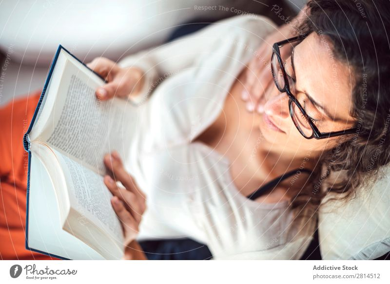 Young couple reading book on couch at home Book Home Literature Sofa Leisure and hobbies closeness Attractive Denim Vantage point Sit Day Life Adults fondness