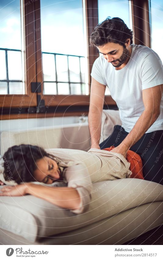 Young couple. Man massaging a woman Woman Barefoot couch massaging Couple Heterosexual couple Easygoing Human being Adults Lie (Untruth) Home Massage Couch