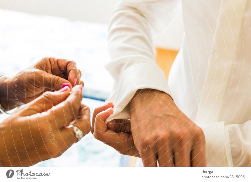 A groom putting on cuff-links in his wedding day. Luxury Elegant Style Wedding Office Business Human being Masculine Man Adults Couple Partner Hand 2 Fashion