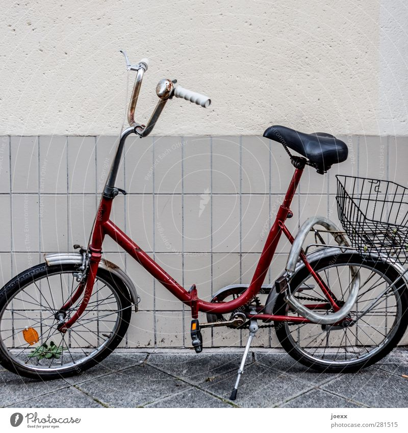 city runabout Wall (barrier) Wall (building) Bicycle Old Hideous Retro Crazy Red Black White Past Folding bicycle chain lock Shopping basket Lock Colour photo