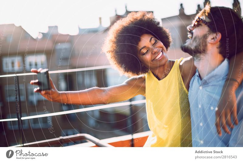 Young couple multicultural taking selfie laughing in love on the rooftop Affectionate African Beautiful boyfriend Caucasian Solar cell Couple dating