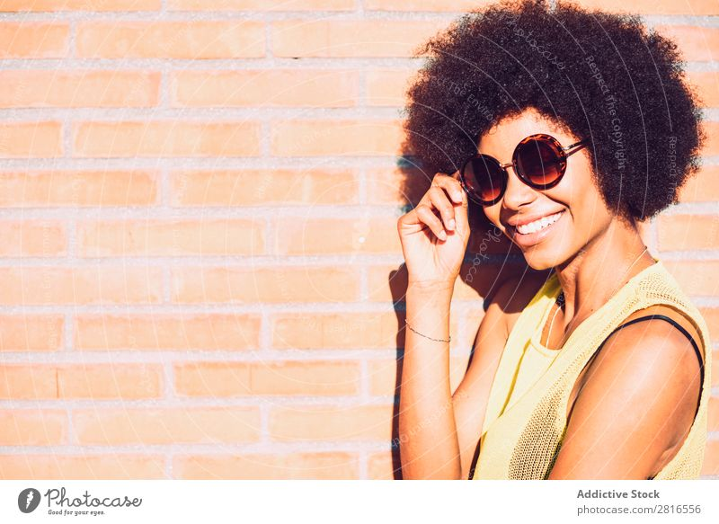 Young beautiful Afro-American woman posing and smiling while standing against brick wall African Charming Brick Model Hand Attractive Curly Sincere Happiness
