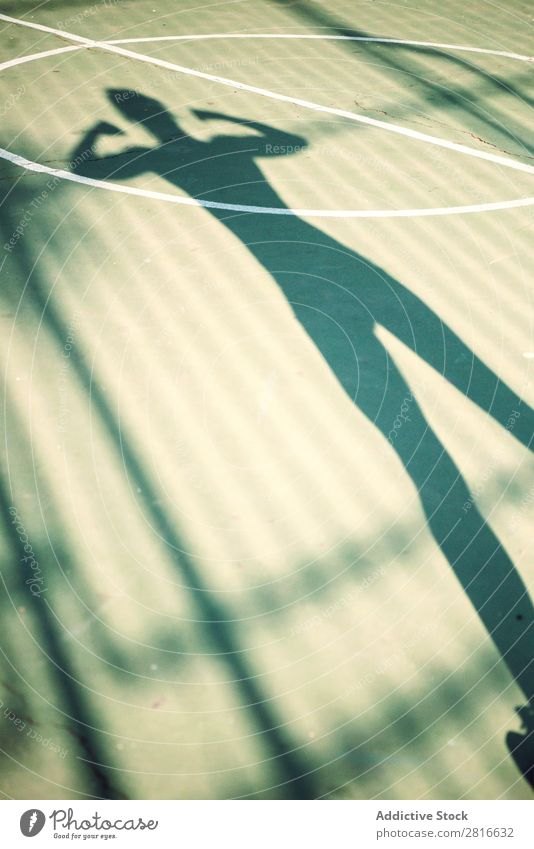Shadow of running woman on a basketball court Fitness Sports Running Stretching Runner Jogger Exterior shot Girl Warmth Lanes & trails Legs Human being Back