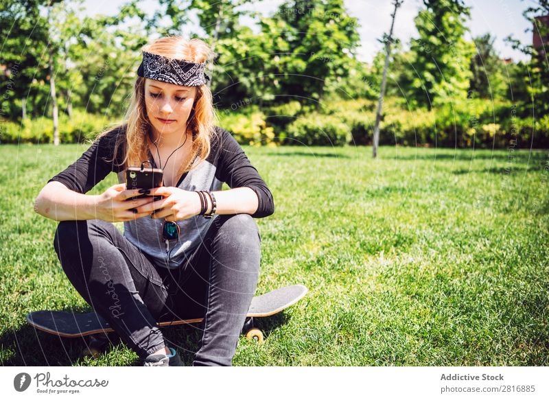 Woman skateboarder listening music from smart phone in a park Music Headphones Joy Park PDA Listening Chinese Culture Cellphone Exterior shot Young woman Sit
