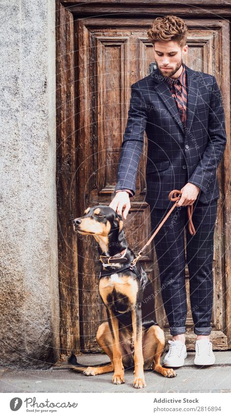 Handsome elegant young fashion man in trendy costume suit with a dog, old wooden door background Suit Man Gentleman Fashion fashionable Clothing Style Model