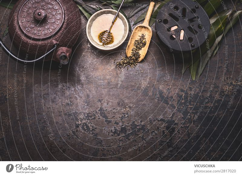 Traditional Asian green tea background with black iron teapot, candle and honey on dark rustic background with copy space, top view traditional asian sencha