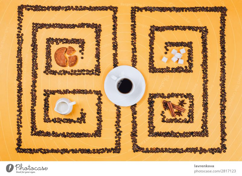 Flatlay of coffee cup in the middle of pattern or labyrinth made of coffee beans with cookies, milker, spices and sugar Cinnamon anise stars Herbs and spices