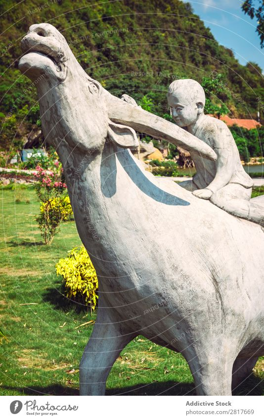Statue of young boy with a buffalo Vietnam Buffalo Exterior shot Thailand Pet Meadow Park Mammal Boy (child) Human being Smiling Asia Love Friendship Hearty