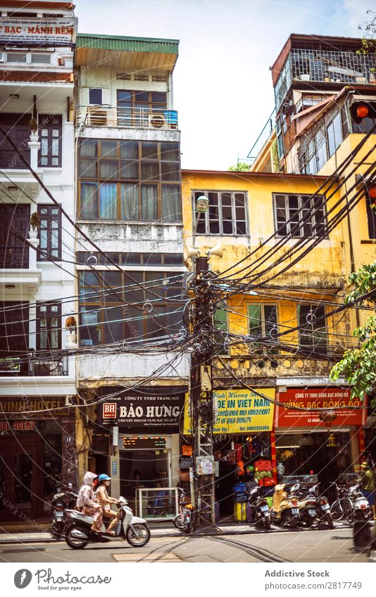 HANOI, VIETNAM - JUNE 17, 2015: Motorcycles running on a typical street in Hanoi with many electric poles and wires across, on June 17, 2015, in Hanoi, Vietmam