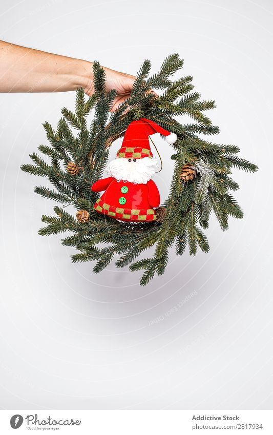 Hand with wreath and toy Christmas & Advent Decoration Wreath Small Toys Santa Claus Green fir Tradition bauble Human being Feasts & Celebrations Winter Home
