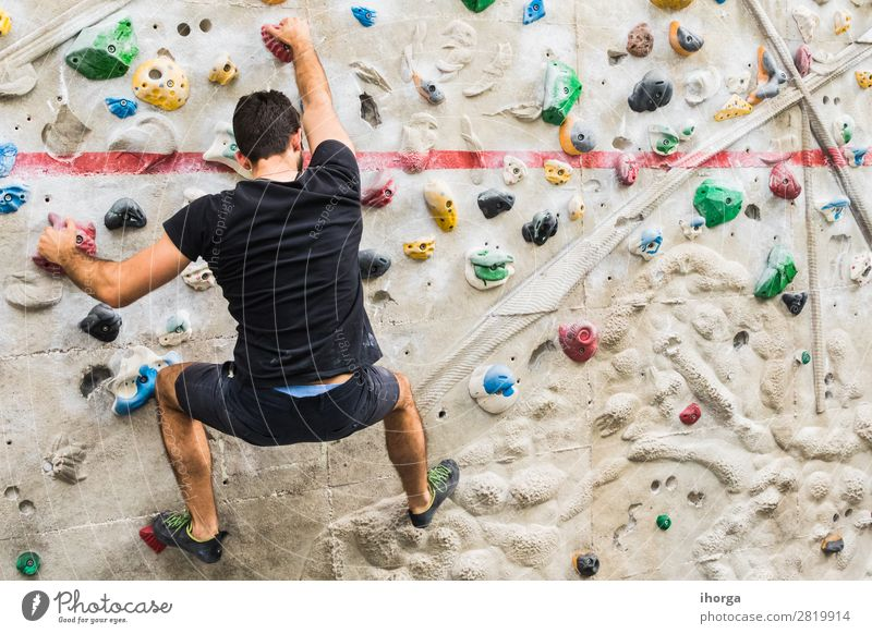 Man practicing rock climbing on artificial wall indoors Lifestyle Joy Leisure and hobbies Sports Climbing Mountaineering Human being Young man