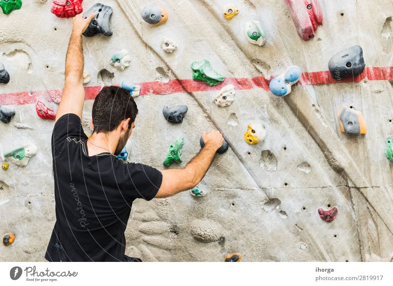 A Man practicing rock climbing on artificial wall indoors. Lifestyle Joy Leisure and hobbies Sports Climbing Mountaineering Adults Hand Fingers 1 Human being