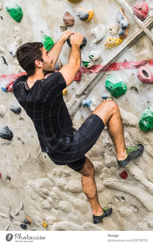 Man practicing rock climbing on artificial wall indoors. Lifestyle Joy Leisure and hobbies Sports Climbing Mountaineering Masculine Adults Hand Feet 1