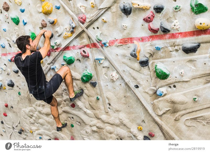 Man practicing rock climbing on artificial wall indoors. Lifestyle Joy Leisure and hobbies Sports Climbing Mountaineering Human being Adults 1 18 - 30 years