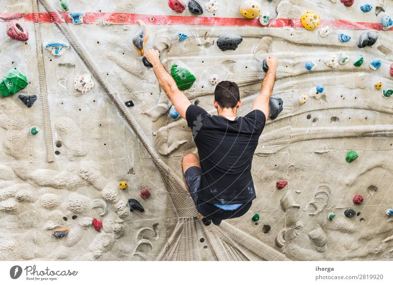 A Man practicing rock climbing on artificial wall indoors. Lifestyle Joy Leisure and hobbies Sports Climbing Mountaineering Adults 1 Human being 18 - 30 years
