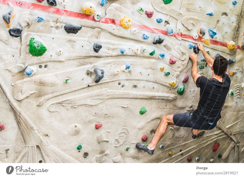 Man practicing rock climbing on artificial wall indoors. Lifestyle Joy Leisure and hobbies Sports Climbing Mountaineering Adults 1 Human being 18 - 30 years