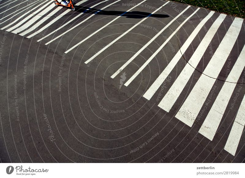 Rolling on strips Asphalt Driving Spring Light Child Playground Signs and labeling Scooter Shadow Summer Playing Stripe Line Copy Space Movement Sports