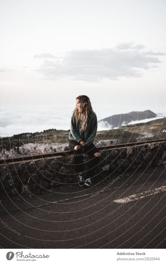Woman sitting at roadside Roadside Sit Fence Mountain Fog Clouds Youth (Young adults) Blonde Street Transport Vacation & Travel Beautiful Wait pretty Earnest