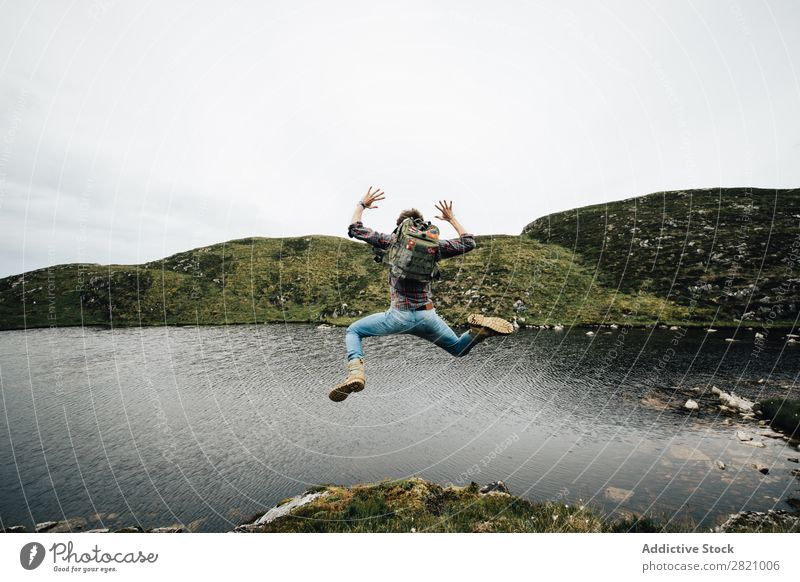 Backpacker jumping on landscape Man backpacker Jump Freedom Landscape Vacation & Travel Mountain Happiness Lakeside Nature above ground Movement Rock