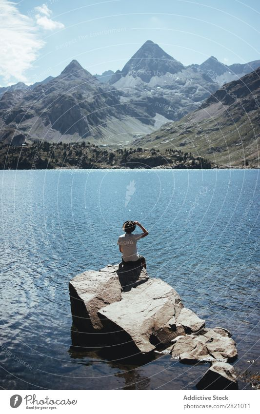 Man on rock looking at lake Lake Rock Sit Looking away Nature Water Vacation & Travel Landscape Human being Lifestyle Youth (Young adults) Mountain Tourism