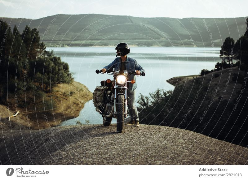 Man on bike posing on landscape Landscape Motorcycle Rock Cliff Wanderlust Transport Vacation & Travel scenery Lake Motorcyclist Stand Freedom Track Adventure