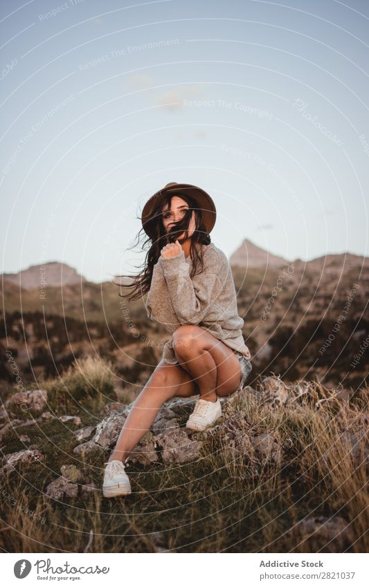 Woman in windy day on rock Rock Sit Mountain Hat Flying Hair Vacation & Travel Top Freedom Youth (Young adults) Nature Tourist Peak Adventure Landscape Action