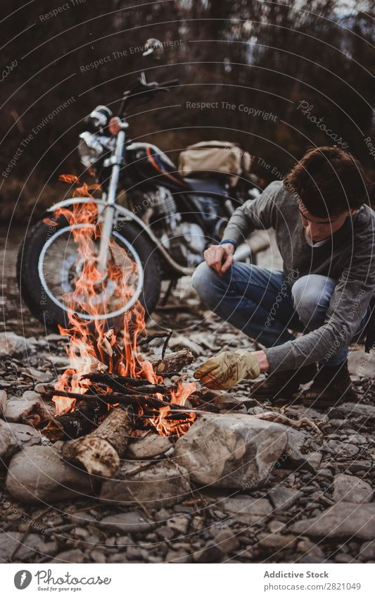 Traveler keeping camp fire Man traveler Fireplace Motorcycle Loneliness Expedition Flame Firewood Wanderlust Action Adventure Traveling Tourism Hiking Transport
