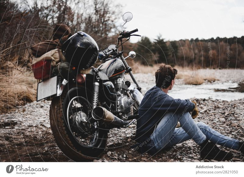 Man sitting near motorcycle Motorcycle Brook Transport Vehicle Freedom Nature Offroad Water Wanderlust Winter Posture traveler Self-confident exploration