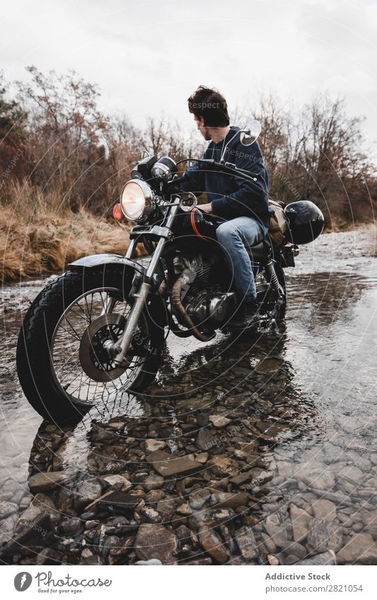 Man crossing creek on motorcycle Motorcycle Brook Transport Vehicle riding Freedom Nature Offroad Water Wanderlust Snow Winter Posture traveler Self-confident