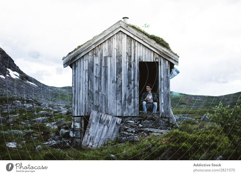 Man sitting in a old house in nature Hut Mountain Remote tranquil terrain bending House (Residential Structure) but Nature Landscape Peaceful Building Exterior