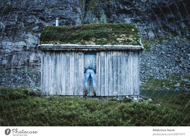 Anonymous man in window of old cabin Man Hut Mountain Remote tranquil Window terrain bending House (Residential Structure) but Nature Landscape Peaceful