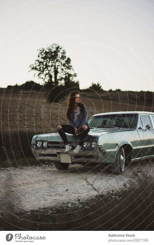 Woman sitting on a car Car Street Field Vacation & Travel Landscape Human being Transport Vehicle Tourism Trip fresh air Gravel Easygoing Open Door Retro Grass