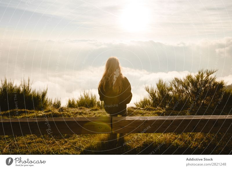 Woman sitting on wooden fence Nature enjoying Freedom Lifestyle Human being Leisure and hobbies Sunlight Sunbeam Day Sky Clouds Grass Recklessness Relaxation