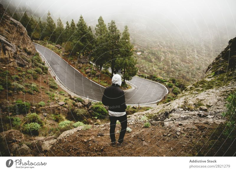 Man looking at mountain road Street Mountain Hill Stand Adventure Nature Vacation & Travel Action Extreme Landscape Success Freedom Top Vantage point Lifestyle