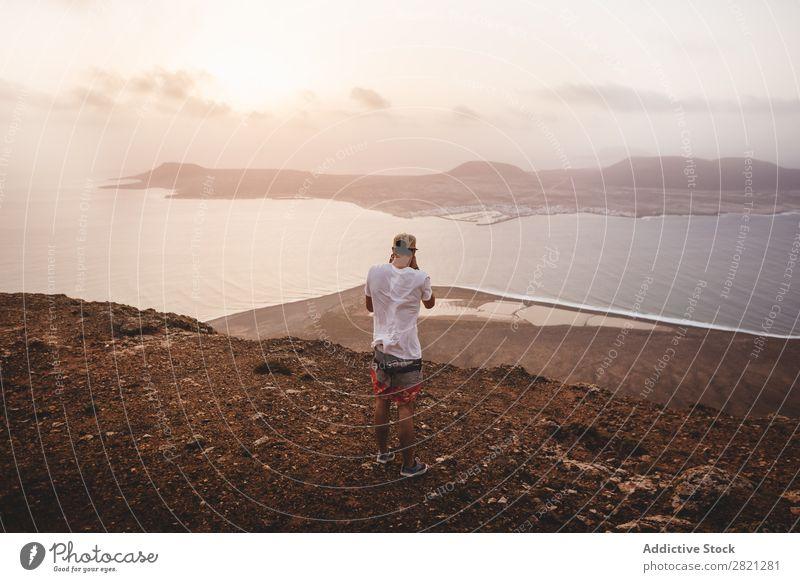 Man taking shot of island shooting Photographer Island Cliff Ocean Vantage point Landscape Water Coast Vacation & Travel Nature seascape Summer Sky Rock Tourism