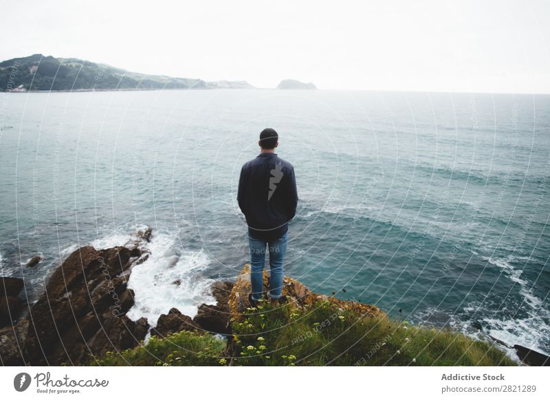 Man on cliff looking at sea Cliff Ocean Vantage point Stand seascape Water Nature Vacation & Travel Landscape Tourism Rock Beautiful Coast Loneliness