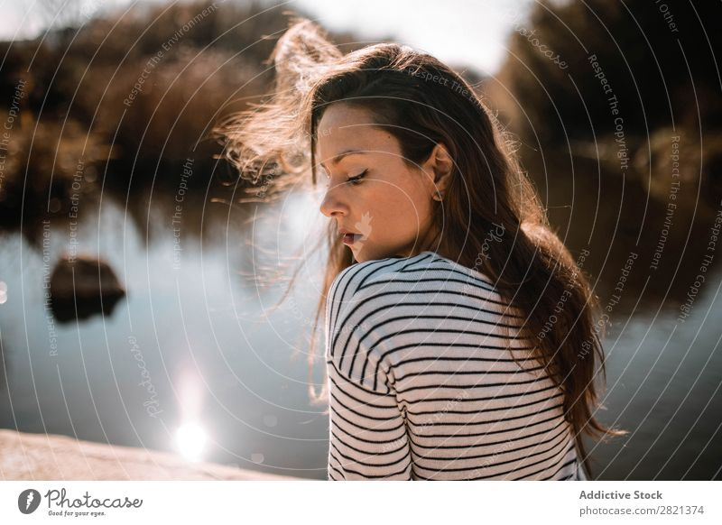 Pretty woman sitting at water looking down Woman pretty Youth (Young adults) Sit Beautiful Sunglasses Water Embankment Sunbeam eyes closed To enjoy Brunette