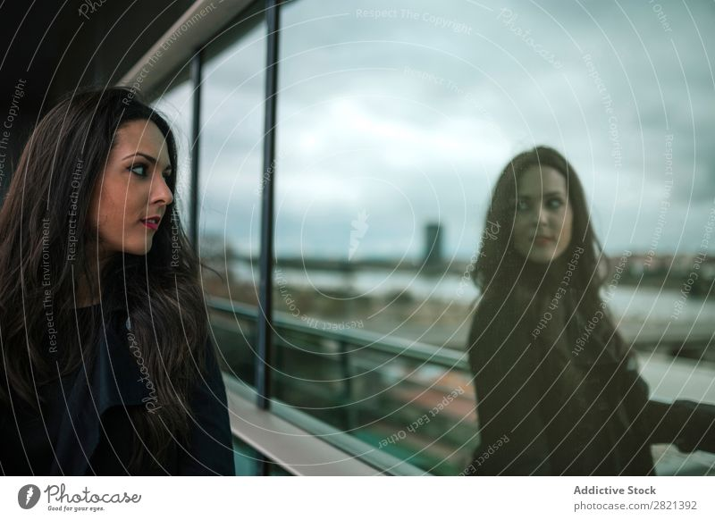 Woman looking at reflection in window pretty Youth (Young adults) Beautiful Stand Window Reflection Building Balcony City Town Brunette Attractive Human being