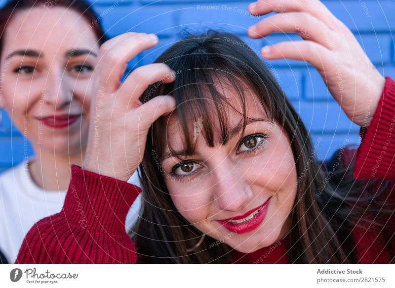 young woman retouching her hair Girl Woman Youth (Young adults) Friendship Happiness confidences Self-confident Attachment Caucasian Smiling Laughter Embrace