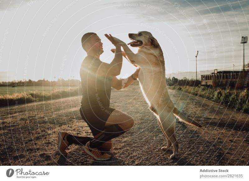 Man playing with his dog at sunset after workout Healthy Pet Human being Runner Fitness Dog Lifestyle Sports Leisure and hobbies Youth (Young adults) Sportswear