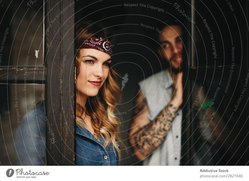 Smiling woman with band on head against of her boyfriend looking at her Couple Tattoo Portrait photograph Window Looking away pretty Beautiful Attractive