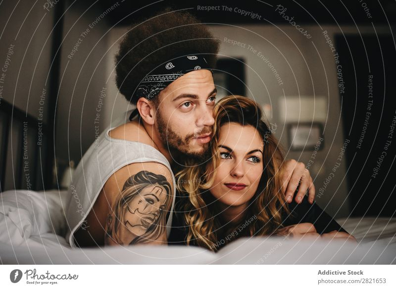 Young couple hugging on bed and looking away Couple Bed Bedroom Smiling Embrace tender Hair and hairstyles Lie (Untruth) Relaxation Home Interior shot Together