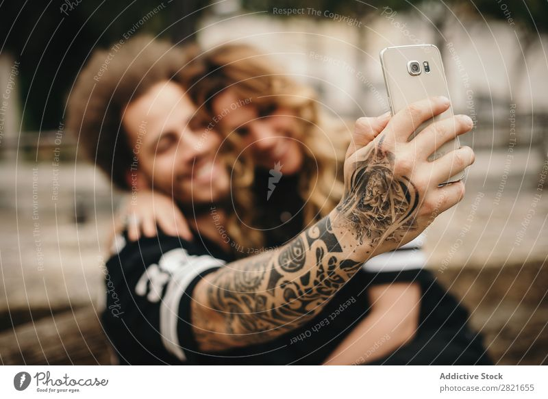 Couple making selfie via smartphone Selfie PDA using Technology focus Smiling Embrace Sit Exterior shot Arm Hand Tattoo Alternative Solar cell Mobile Day