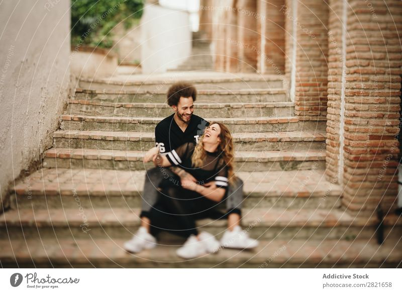 Couple laughing while hugging on steps in city Laughter having fun Portrait photograph Street Sit Together Embrace Steps Rural Stairs Cheerful candid Happy