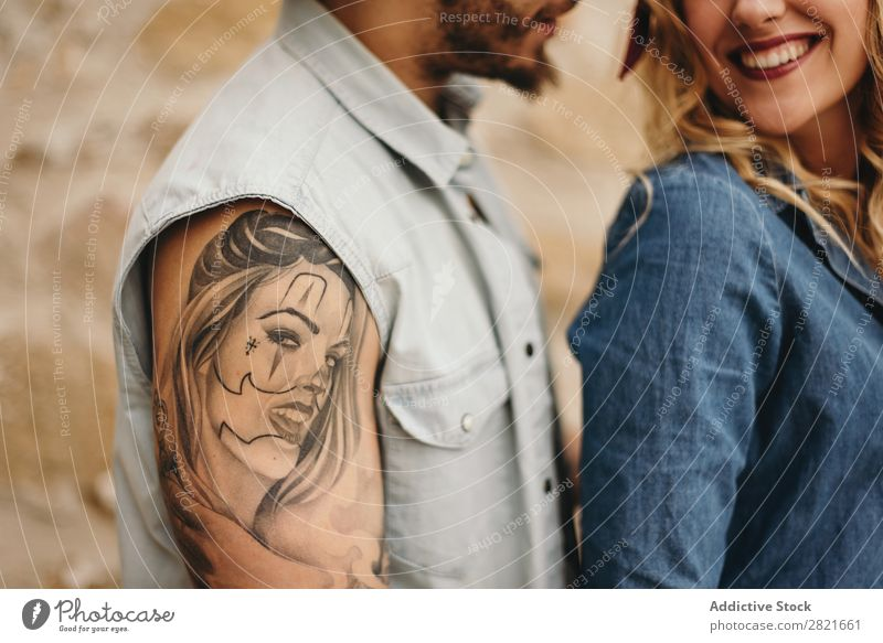Couple in close up. Man with tattoo of his girlfriend's face Smiling Tattoo Portrait photograph Face Girl Unrecognizable Close-up body part Arm Shoulder