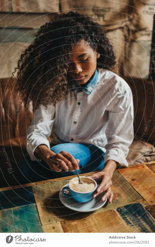 Ethnic woman stirring cup of coffee Woman pretty Beautiful Black Curly Youth (Young adults) Stir Coffee Cup latte Brunette Attractive Human being
